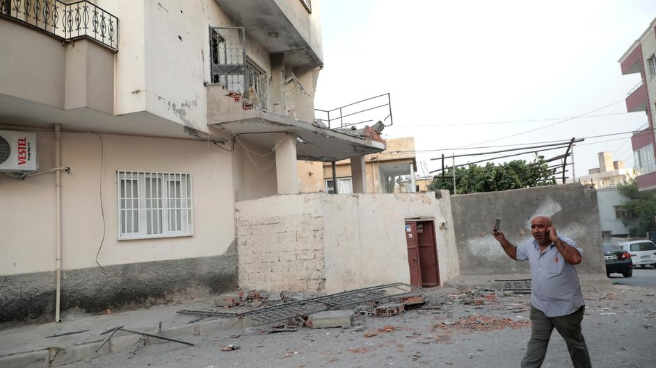 A man reacts after an apartment building hit by a rocket fired from Syria, in Nusaybin