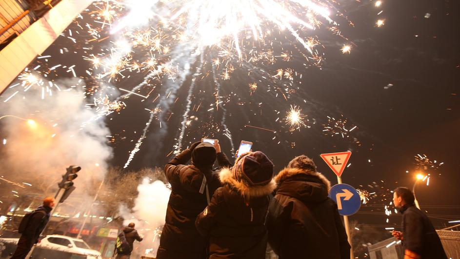 People watch fireworks explode on the eve of the Spring Festival, in Beijing