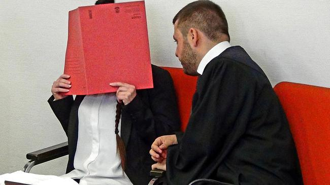 Defendant Jennifer W. covers her face as she waits for the start of the trial in Munich