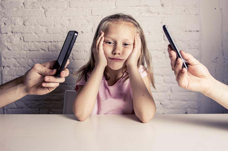 hands of network addict parents using mobile phone neglecting little sad ignored daughter bored | Autor: Dreamstime