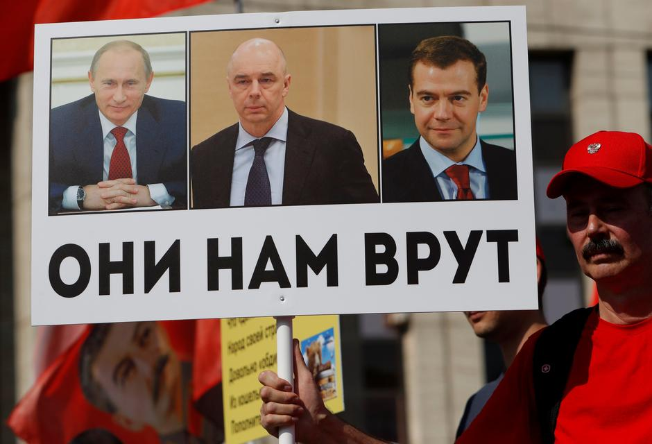 A man holds sign depicting Russian President Putin, FM Siluanov and PM Medvedev during a protest against a proposed increase of the retirement age in Moscow | Autor: SERGEI KARPUKHIN/REUTERS/PIXSELL/REUTERS/PIXSELL
