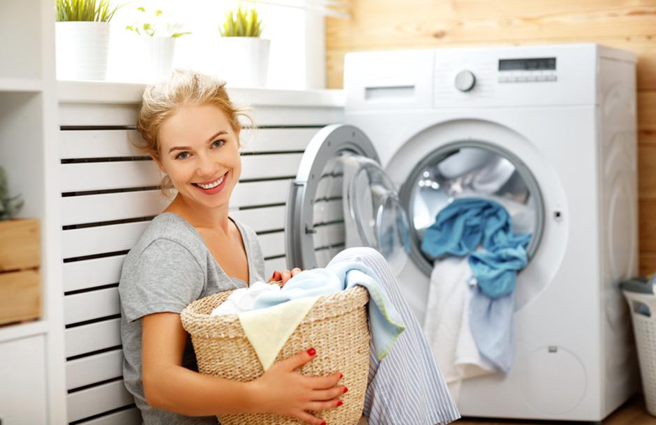 Happy housewife woman in laundry room with washing machine | Autor: Evgeny Atamanenko