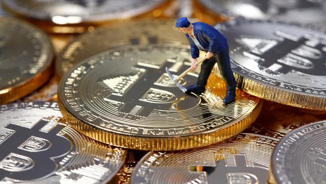 A small toy figure is seen on representations of the Bitcoin virtual currency in this illustration picture