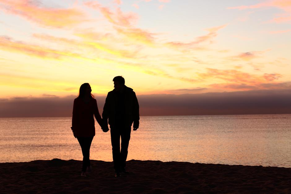 Couple silhouettes walking together at sunset | Autor: Dreamstime