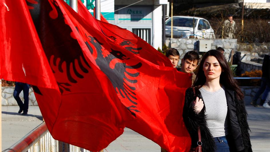 A girl passes next to Albanian flags ahead of tomorrow's 10 year independence celebration in Kacanik