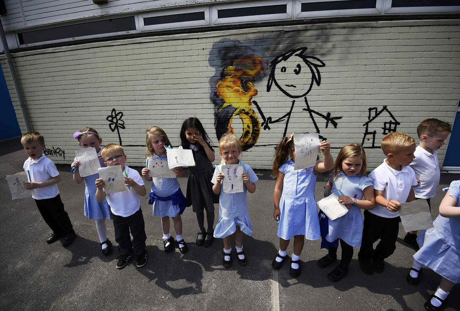 Reception class school children show off their drawings of a mural attributed to Banksy in Bristol | Autor: DYLAN MARTINEZ