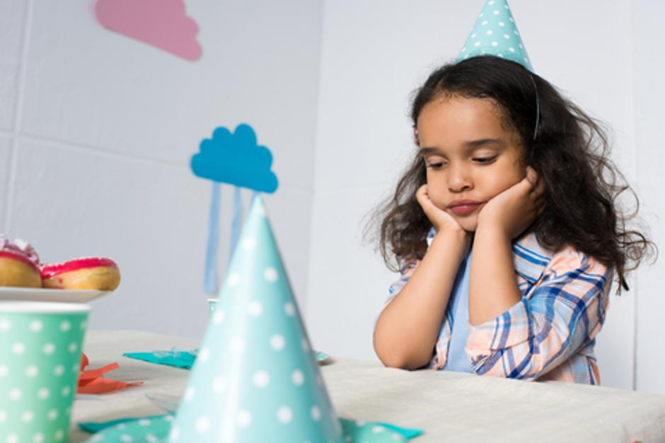upset little african american girl sitting alone at birthday table | Autor: Dreamstime
