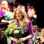 Slovakia's presidential candidate Zuzana Caputova receives flowers after winning the presidential election, at her party's headquarters in Bratislava