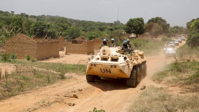 United Nations peacekeeping force vehicles drive by houses destroyed by violence in September, in the abandoned village of Yade, Central African Republic