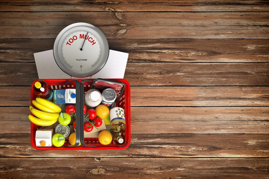 Groceries in a shopping basket on weight scale. Overnutrition, m | Autor: Dreamstime