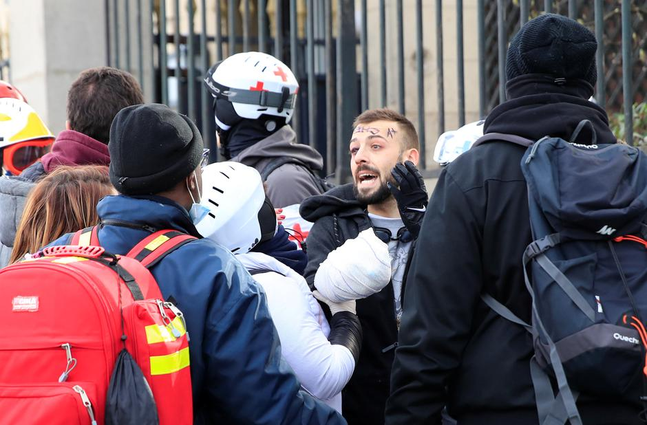 "An injured protester is given help during a demonstration by the ""yellow vests"" movement in Paris 