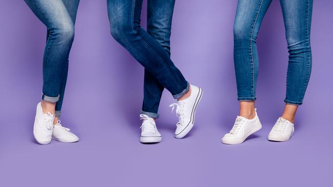 Cropped closeup photo of three people's legs wearing denim dark blue jeans trousers pants standing on the floor isolated violet background