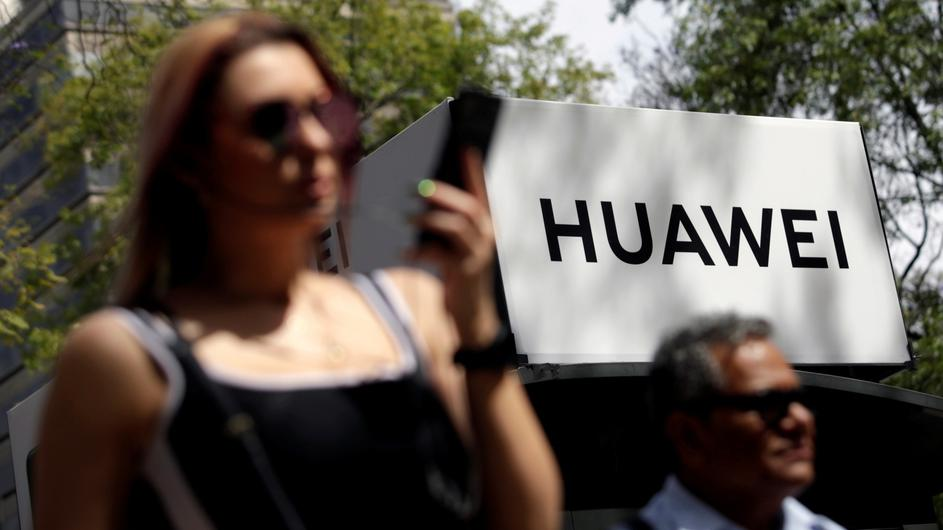 FILE PHOTO: People walk past a Huawei company logo at a bus stop in Mexico City