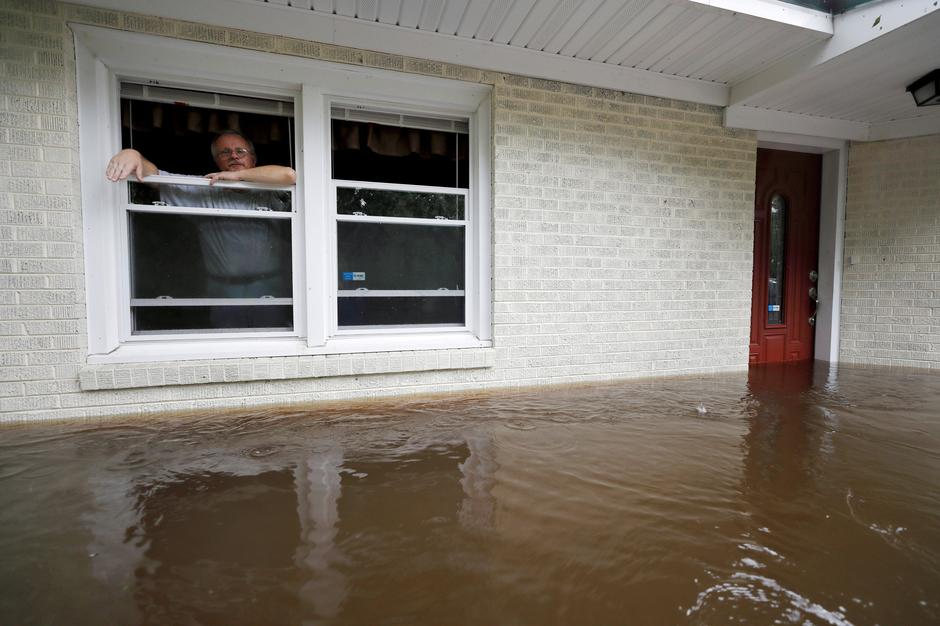 Gavrilovic peers out the window of his flooded home while considering whether to leave with his wife and pets as waters rise in North Carolina | Autor: JONATHAN DRAKE