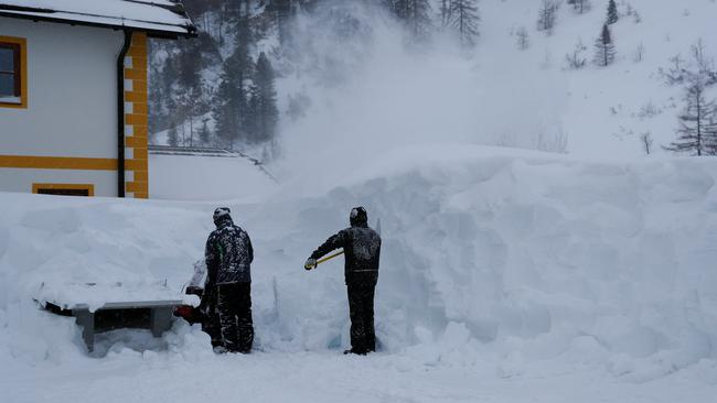Two workers remove snow after heavy snowfall in Obertauern