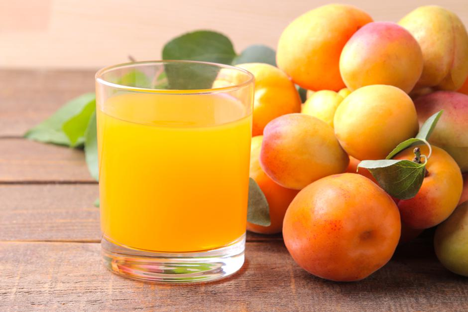 Apricot juice in a glass cup next to fresh apricots on a brown wooden background | Autor: Dreamstime