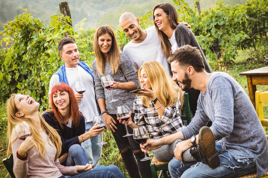 Happy friends having fun outdoor - Young people drinking red win | Autor: Dreamstime