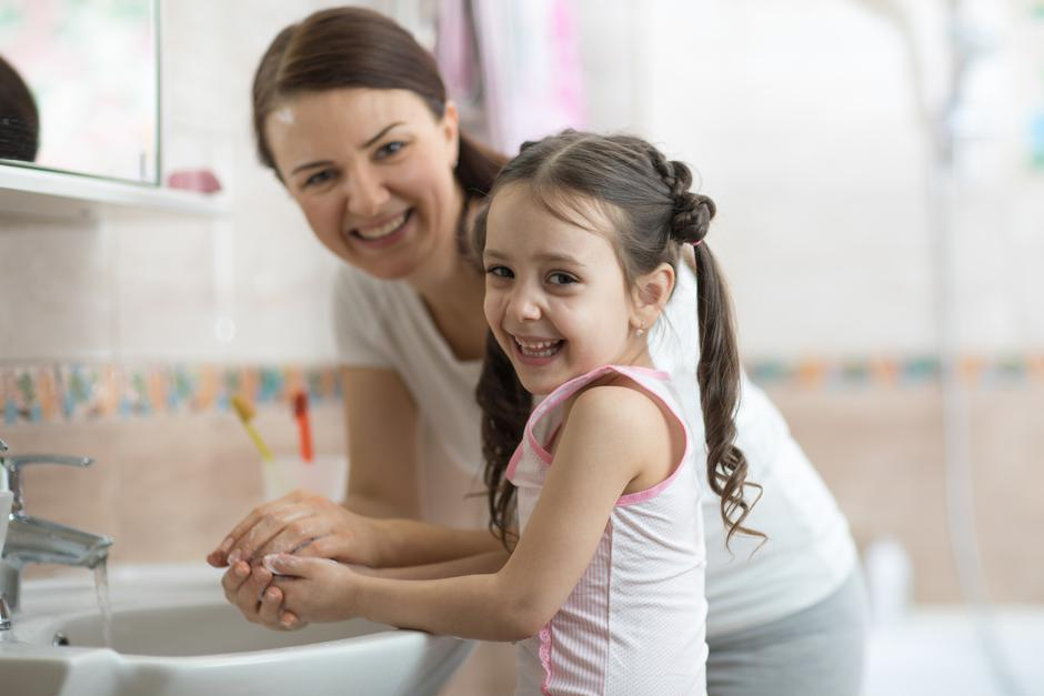kid with mom washing her hands in bathroom | Autor: Dreamstime