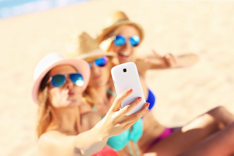 Group of friends taking selfie on the beach | Autor: Kamil Macniak