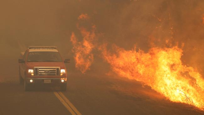FILE PHOTO: A firetruck rushes past flames that overran a road at the River Fire in Lakeport