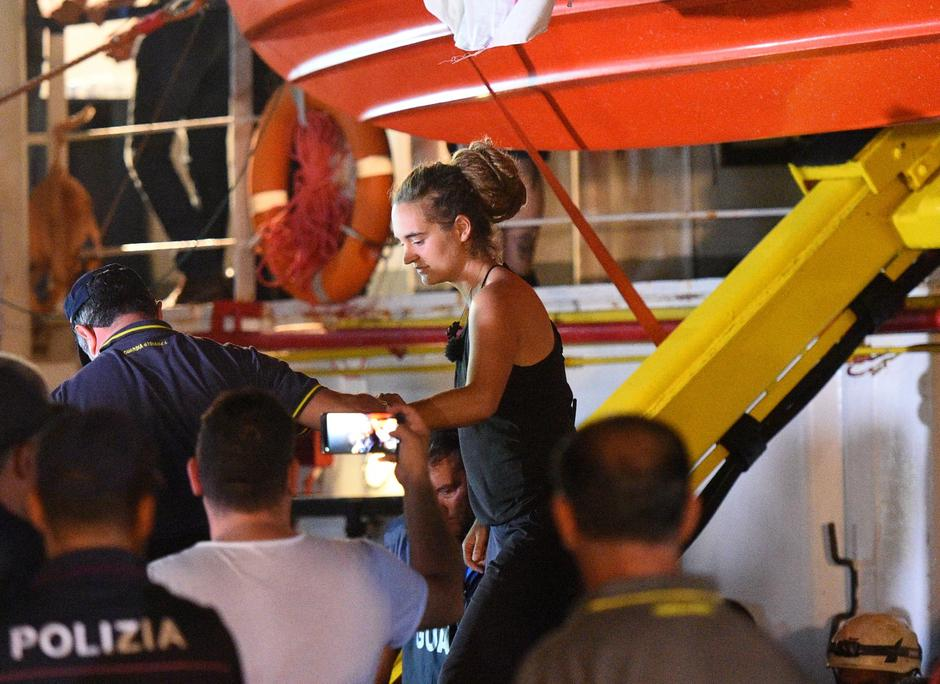 Carola Rackete, the 31-year-old Sea-Watch 3 captain, is escorted off the ship by police and taken away for questioning, in Lampedusa | Autor: GUGLIELMO MANGIAPANE/REUTERS/PIXSELL/REUTERS/PIXSELL