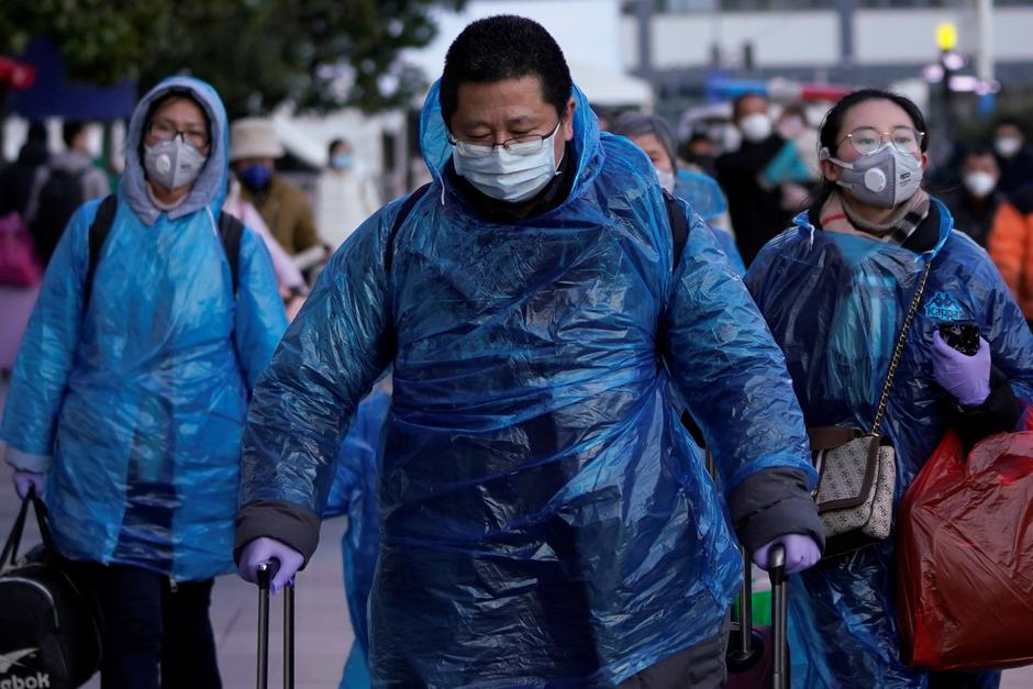 People wear face masks and plastic raincoats as a protection from coronavirus in Shanghai | Autor: ALY SONG