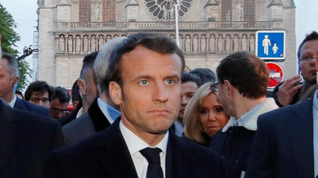 French President Emmanuel Macron walks near the Notre Dame Cathedral as its burns in Paris