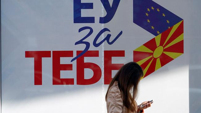 "A woman passes next to posters reading ""EU for you"" for the referendum in Macedonia on changing the country's name in Skopje"