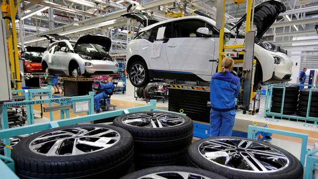 FILE PHOTO: A worker mounts a tyre at the serial production BMW i3 electric car in the BMW factory in Leipzig