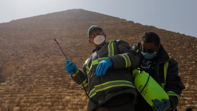 Members of the medical team prepare to spray disinfectant as a precautionary move amid concerns over the coronavirus disease (COVID-19) outbreak at the Great Pyramids, Giza, on the outskirts of Cairo