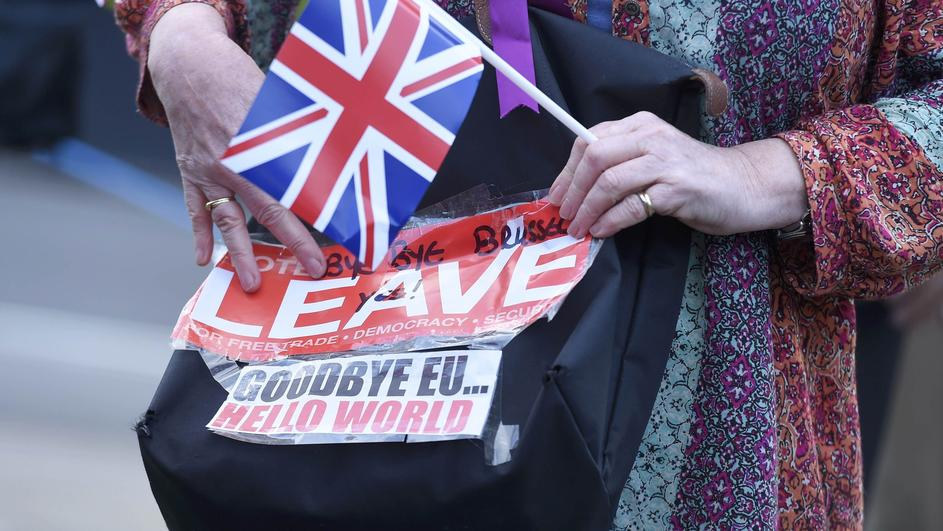 A vote leave supporter holds a poster in Westminster, London
