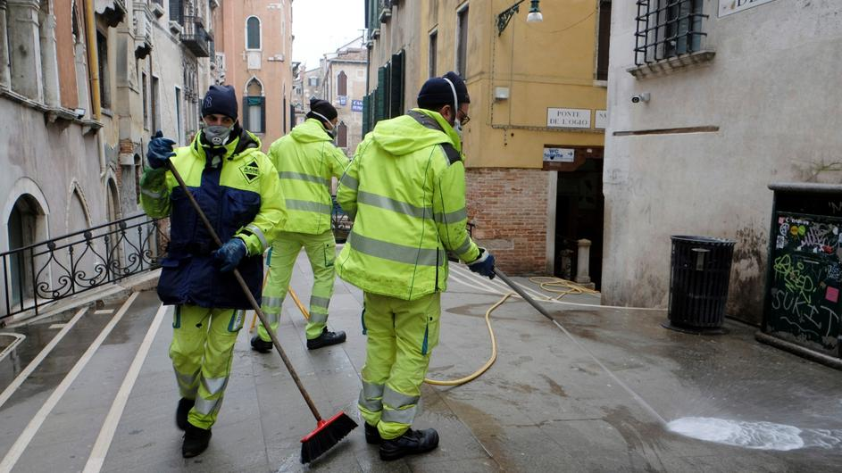 Workers sanitise a bridge as a measure against the coronavirus disease (COVID-19) in Venice