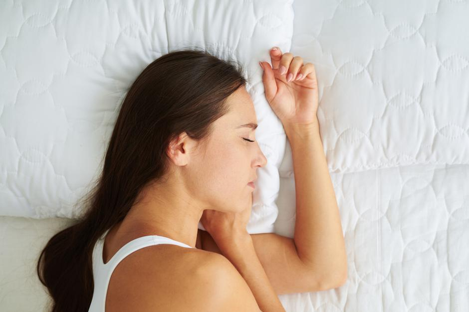 Young beautiful woman sleeping lying on the side in the bed | Autor: Dreamstime