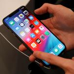 A customer tests a smartphone during the launch of the new iPhone XS and XS Max sales at a shop in Moscow