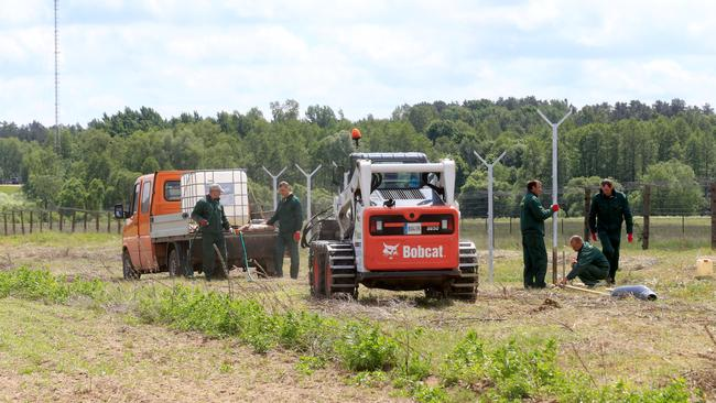 Workers install poles for fence near Sudargas border crossing point with Russia in Ramoniskiai