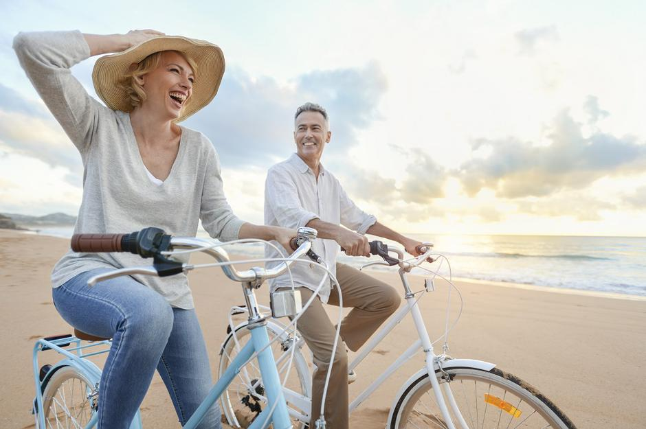 Mature couple cycling on the beach at sunset or sunrise. | Autor: courtneyk