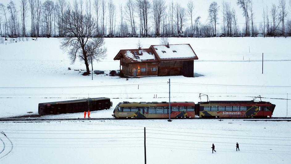 A carriage of the MOB train is pictured lying on its side after if was pushed out of the tracks by gusts of wind during storm Eleanor near Lenk