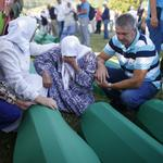 People mourn near coffins of their relatives, who are newly identified victims of the 1995 Srebrenica massacre, which are lined up for a joint burial in Potocari near Srebrenica