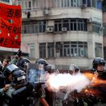 Police officers fire tear gas as anti-extradition bill protesters demonstrate in Sham Shui Po neighbourhood in Hong Kong,