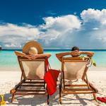 Couple in loungers on beach at Maldives