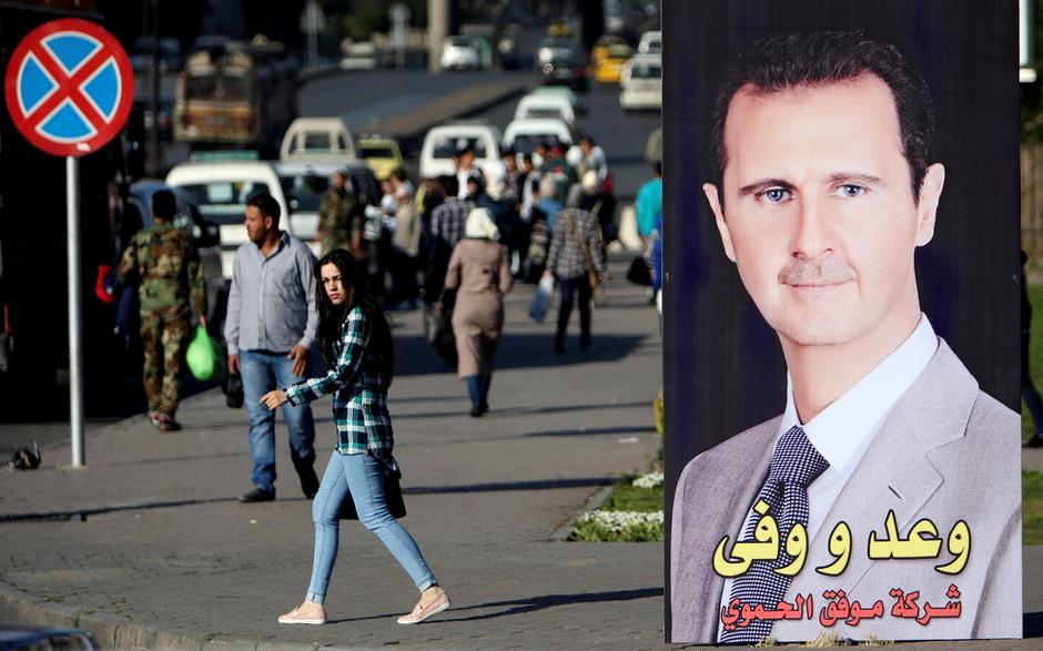 A woman walks near a picture of Syrian President Bashar al Assad in Damascus | Autor: ALI HASHISHO/REUTERS/PIXSELL/REUTERS/PIXSELL