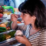 Woman eating unhealthy food from the fridge at night