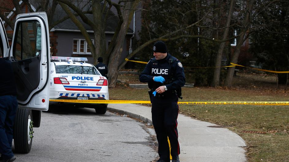 Police officers guard the grounds of a house they searched in Toronto