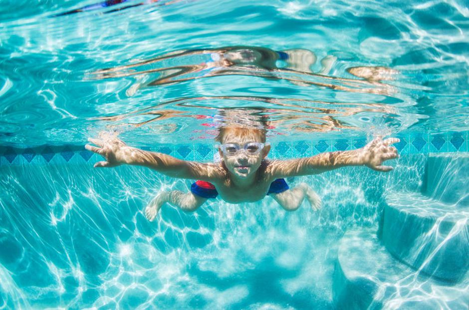 Young Boy Diving Underwater in Swimming Pool | Autor: EpicStockMedia