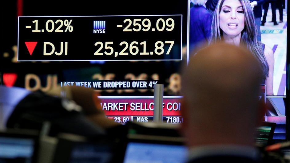 A trader looks at a screen that displays the Dow Jones Industrial Average on the floor of the NYSE in New York