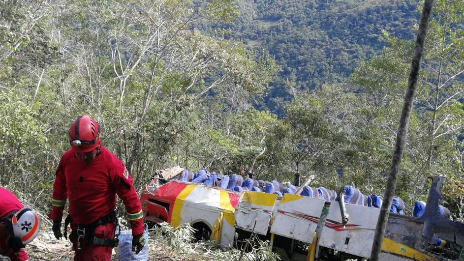 Members of a rescue team are seen next to a crashed bus where dozens of people died and others were injured, in the route La Paz-Yungas north of La Paz