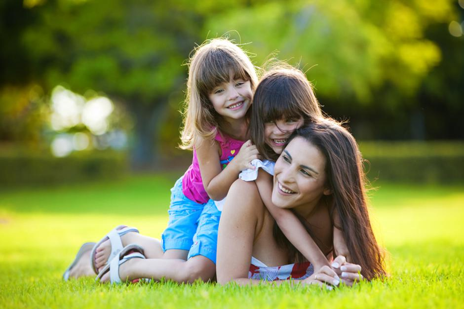 Young mother and two daughters playing outdoors | Autor: Dreamstime