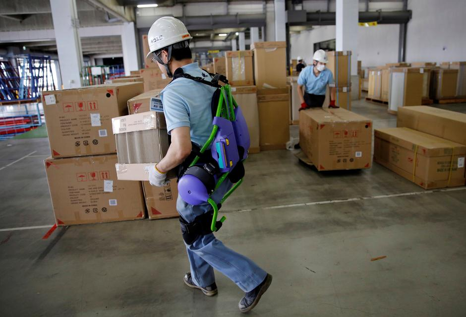 Okutani, 57, a contract worker of Ueda Co., Ltd., wears an Atoun Inc. Power Assist Suit, as he works at a distribution center in Kawasaki | Autor: TORU HANAI