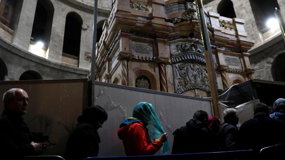 Visitors stand near the newly restored Edicule, the ancient structure housing the tomb, which according to Christian belief is where Jesus's body was anointed and buried, at the Church of the Holy Sepulchre in Jerusalem's Old City