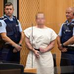 Brenton Tarrant, charged for murder, making a sign to the camera during his appearance in the Christchurch District Court